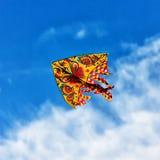 Voo brilhante colorido do papagaio no vento no céu azul Fotos de Stock Royalty Free