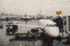 Voo cancelado durante o conceito das condições meteorológicas Aviões na porta sob a chuva maciça Voo do atraso foto de stock