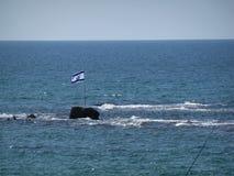 Voo da bandeira de Israel acima da rocha pequena no mar Fotos de Stock Royalty Free