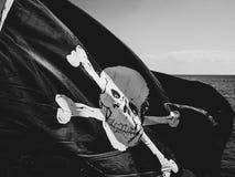 Voo da bandeira de pirata de Jolly Rogers de um barco de navigação foto de stock