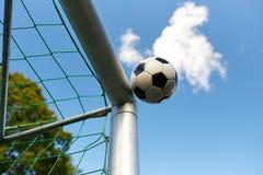 Voo da bola de futebol na rede do objetivo do futebol sobre o céu Imagem de Stock Royalty Free