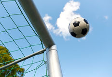 Voo da bola de futebol na rede do objetivo do futebol sobre o céu Fotos de Stock Royalty Free