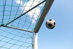 Voo da bola de futebol na rede do objetivo do futebol sobre o céu Imagens de Stock