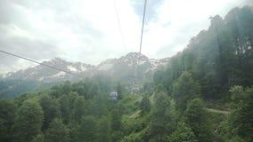 Voo da câmera sobre montanhas Cume de Aibga Teleférico com cabines vídeos de arquivo