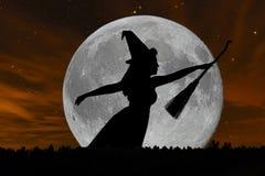 Voo da silhueta da bruxa de Dia das Bruxas com cabo de vassoura Lua cheia Fotos de Stock