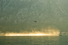 Voo de combate ao fogo do helicóptero à superfície da àgua Foto de Stock Royalty Free