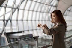 Voo de espera da mulher e vista do relógio esperto no aeroporto fotografia de stock royalty free