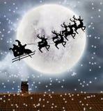 Voo de Santa sobre a parte superior da Lua cheia e do telhado imagens de stock