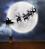 Voo de Santa sobre a parte superior da Lua cheia e do telhado fotografia de stock royalty free