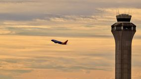 Voo de Southwest Airlines Boeing B737 na distância com a torre de controlo na parte dianteira imagens de stock royalty free