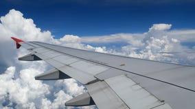 voo do avião da metragem 4K asa de um voo do avião acima das nuvens do branco e do céu azul vista aérea bonita da janela vídeos de arquivo