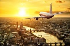 Voo do avião dos passageiros acima da cidade de Londres na luz do por do sol fotografia de stock royalty free