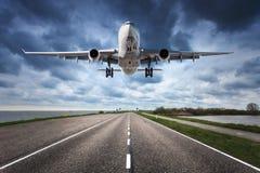 Voo do avião no céu nebuloso e na estrada imagens de stock