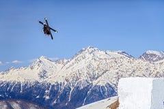 Voo do esquiador de um salto de esqui que faz a figura no céu azul e no fundo nevado dos picos de montanha Fotos de Stock