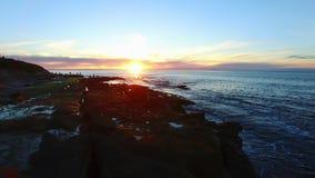 Voo do helicóptero acima da praia da angra de La Jolla no por do sol filme