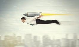 Voo do homem de negócio do super-herói com o foguete do bloco do jato acima do cit Foto de Stock Royalty Free