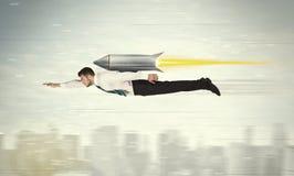 Voo do homem de negócio do super-herói com o foguete do bloco do jato acima do cit Fotos de Stock Royalty Free