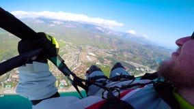 Voo do homem no paraplane no céu, nas nuvens e na paisagem da skyline Voo do paraglider do ponto de vista no paraplane parachutin video estoque