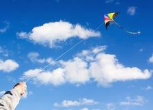 Voo do papagaio em nuvens bonitas de um céu Foto de Stock