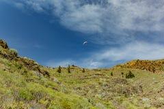 Voo do Paraglider sobre os picos de montanhas contra o céu azul brilhante Dia ensolarado Céu azul claro e algumas nuvens acima do foto de stock