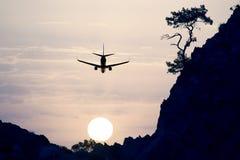 Voo do plano de avião de passagem no céu da noite no por do sol foto de stock royalty free