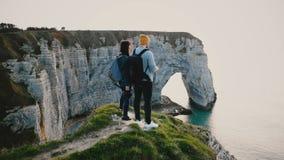 Voo do zangão em torno dos pares felizes novos do turista com as trouxas que olham o mar épico do por do sol sobre o penhasco da  filme
