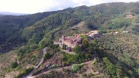 Voo lindo do zangão sobre uma vila pequena italiana situado nos montes, com alguma arquitetura medieval, Europa, noite macia filme