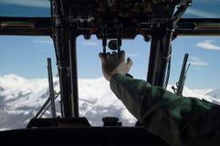 Voo militar do helicóptero através das montanhas nevadas brancas Foto de Stock