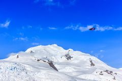 Voo plano vermelho pequeno entre nuvens sobre picos e geleiras da neve fotos de stock royalty free