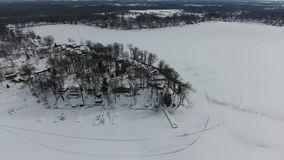 Voo sobre casas cobertos de neve ao longo das proximidades do lago congeladas vídeos de arquivo