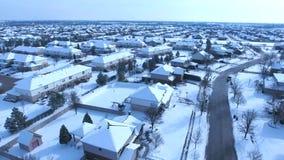 Voo sobre casas residenciais cobertos de neve e jardas ao longo da rua suburbana video estoque