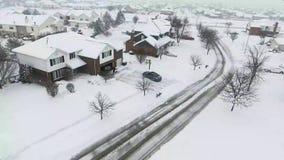 Voo sobre casas residenciais cobertos de neve e jardas ao longo da rua suburbana vídeos de arquivo
