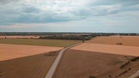 Voo sobre a estrada rural entre campos de cereal maduros para casas da quinta e celeiros filme
