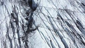 Voo sobre a geleira de Solheimajokull em Islândia do sul Opinião aérea do zangão da fissura e da cinza vulcânica preta capturadas video estoque