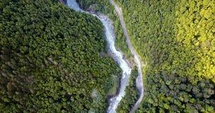 Voo sobre o desfiladeiro da montanha Estrada ao longo do rio, nas madeiras vídeos de arquivo