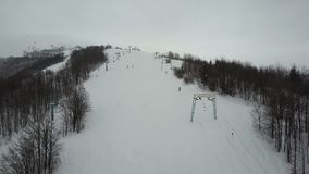 Voo sobre os povos que usam o elevador de esqui nas montanhas Opinião aérea Ski Resort filme