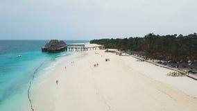 Voo sobre a praia larga do paraíso com o oceano branco da areia e dos azuis celestes no dia nebuloso video estoque