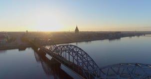 Voo velho do zangão de Riga da cidade do tempo do nascer do sol da manhã da cidade de Riga sobre estradas e ponte do trem filme