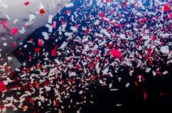 Voo vermelho e branco dos confetes na noite Imagem de Stock