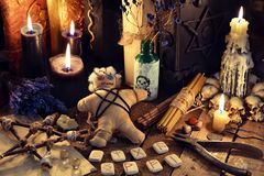 Voodoo doll, black candles, pentagram and old books on witch table. Occult, esoteric, divination and wicca concept. Mystic and vintage background with old stock photography