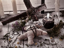 Voodoo doll with cross, herbs and black candle Stock Photos