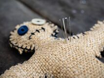 A voodoo doll made of burlap, with buttons for eyes, pierced with many needles right through the heart, close-up. The concept of