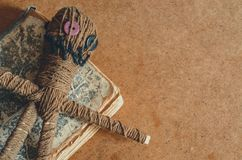 Voodoo doll with needles and old book on rough textured background
