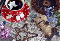 Voodoo doll with pentagram, cup of tea, mysterious objects and flowers. Occult, esoteric and divination still life. Halloween background with vintage objects and stock photos