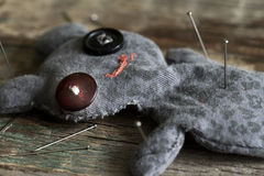 Voodoo doll and pins on old vintage wooden floor Stock Photography