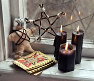 Voodoo doll, tarot cards, pentagram and black candles by old window. Occult, esoteric, divination and wicca concept. Mystic and vintage background with old stock image
