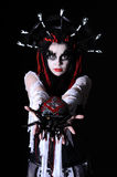 Voodoo shaman. Portrait of woman with voodoo shaman make-up hold toy spider isolated on black Stock Images
