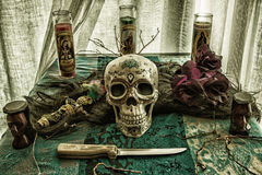 Voodoo Skull Ritual Evil. Voodoo related objects on a table including a skull, a knife and candles royalty free stock photography