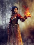 Voodoo sorceress with a flame. Young voodoo sorceress standing in a dark forest at night and holding a flame in her hand stock illustration