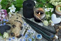 Voodoodocka, svartstearinljus, blommor och mystiska objekt arkivfoto
